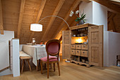 Medallion chair at dining table in modern farmhouse parlour with sloping ceiling