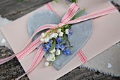 Greetings card decorated with ribbon, lily-of-the-valley and forget-me-nots on love-heart
