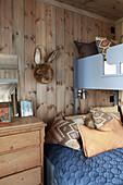 Bunk beds in rustic children's bedroom with wood-clad walls