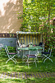 Garden table and beach chair in summery garden behind house