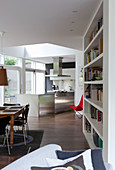 Bookcase, dining area and kitchen in open-plan interior