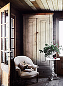 Sessel und runder Beistelltisch vor Holzschrank