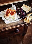 Käse, Cracker und Weintraube auf rustikalem Tisch