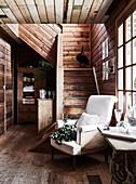 Französischer Sessel vor Treppenaufgang in rustikaler Diele
