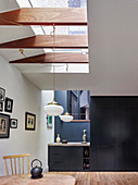 Skylight, wooden beams and fitted cupboards in dining room