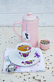 Violet infusion in floral teacup and insulated teapot