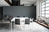 Double table and chairs in industrial loft apartment with bicycle against grey wall in background