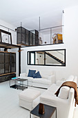 White sofas in living area and view of gallery in industrial-style loft apartment
