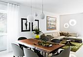 Esstisch mit Mahagoni-Platte und Designer-Schalenstühle, im Hintergrund Ledersofa