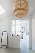 White walls and bamboo lightshade in hallway
