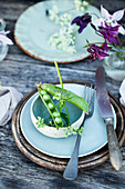 Rural table setting with pea pods as place cards, early summer bouquet