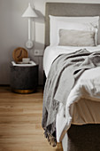 Bedside table and wall-mounted lamp next to bed with white bed linen