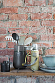 Kitchen utensils on shelf on rustic brick wall