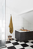 Bathtub on chequered floor below sloping ceiling