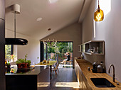 Open-plan kitchen, dining table and access to garden in modern interior