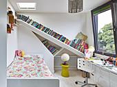 Slanted bookshelves in child's bedroom decorated in white