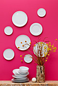 White plates on hot-pink wall and yellow flowers in tree-stump vase
