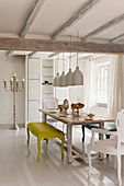 Large white pendant lights hanging above an antique cherry wood dining table with brightly coloured Louis benches and chairs