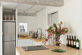 Yellow sand coloured concrete work surfaces in kitchen with vase of flowers and fridge