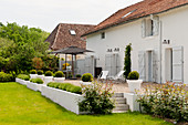 Exterior facade of converted barn with shutters and gravel terrace