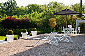 Deck chairs and parasols on gravel terrace