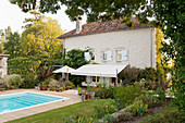 Outdoor swimming pool in the garden of converted French mill with awning, lawn and flower beds