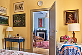 Artwork on yellow wall and view through doorway to carved wooden chair