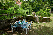 Circular table and chairs in garden on riverbank