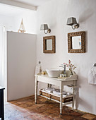 Pair of wicker-framed mirrors above washstand and original 18th-century terracotta floor tiles