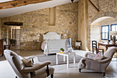 Spacious attic bedroom with upholstered furniture and stone walls