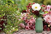 Bouquet of dahlias and unripe blackberries