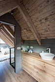 Wooden washstand in ensuite bathroom with view into bedroom