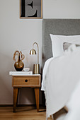 Vase and lamp on wooden bedside table next to bed with headboard