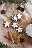 Cinnamon star biscuits, cinnamon sticks, star anise, candle and fir branches on brown paper