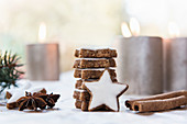 Stack of cinnamon star biscuits, cinnamon sticks, star anise and lit candles in background