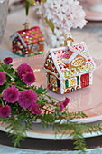Christmas-tree decoration in shape of gingerbread house on plate