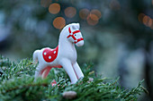Red-and-white rocking horse ornament on fir branches against blurred background