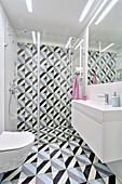 Tiles with graphic pattern on floor and wall of modern bathroom