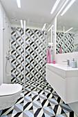 Grafisch gemusterte Fliesen an Boden und Wand im modernen Bad