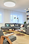 Grey corner sofa and round coffee table in modern living room