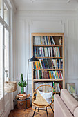 Bookcase, rattan chair and standard lamp next to window in living room