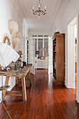 Old wooden table and bookcase in hallway with wooden floor