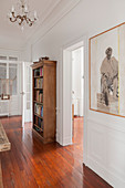 Artwork and bookcase in hallway with wooden floor