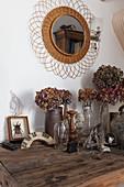 Vasen mit Trockenblumen auf altem Holztisch, darüber Wandspiegel