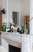 Dekoobjekte und Lampe mit grünem Glasfuß auf Kaminsims mit Spiegel