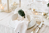 White Christmas place setting decorated with sprig of fir