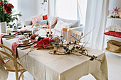 Table set for Christmas meal with red paper star, larch branches and vase of amaryllis