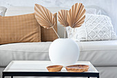 DIY palm leaves made from brown paper in white spherical vase on coffee table