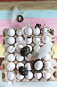 Painted eggs, feathers and twig on crate of white eggs