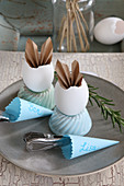 Table decorated in vintage style with folded paper bunny ears in egg shells